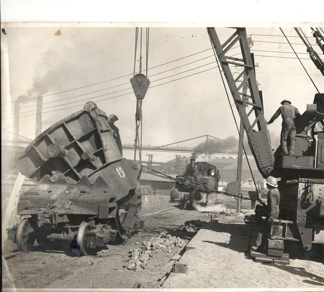 No 1. Steam Crane tipping a Slag Pot in the early days, notice the Steam Loco waiting away from the pot for safety.